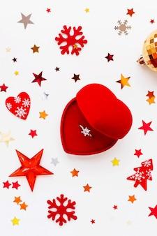 Navidad y vacaciones con adornos y anillo de compromiso con diamantes en caja de regalo. bolas brillantes, copos de nieve de fieltro y confeti estrella. vista plana, vista superior.