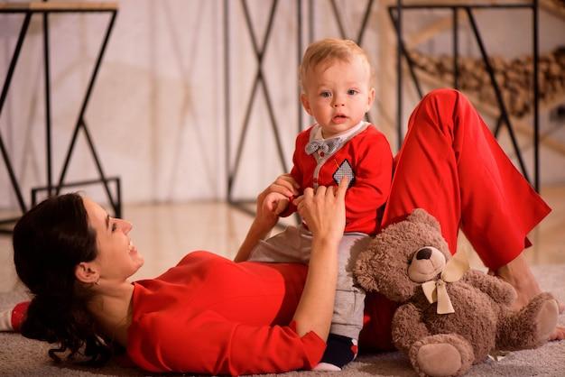 Navidad, vacaciones, concepto de familia - madre feliz y juego de niños en casa.
