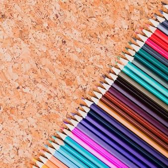 Neat fila de lápices de colores colocados en diagonal sobre fondo de corcho