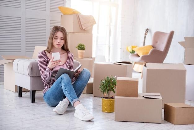 Necesita ayuda. encantadora mujer joven sentada en el suelo y comprobando el número de empresas de mudanzas antes de salir de la casa