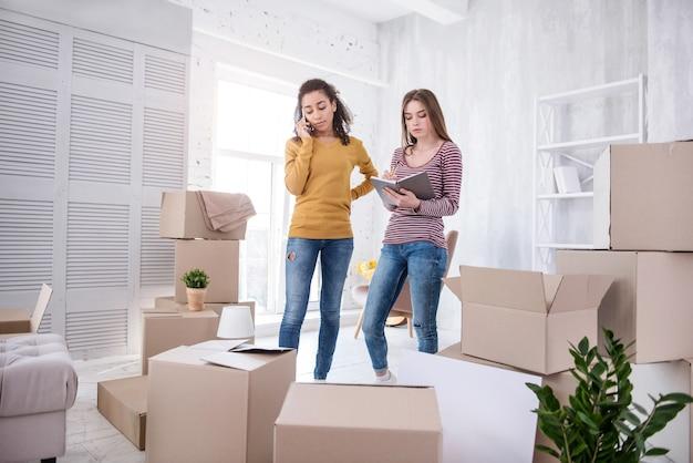 Necesito ayuda. hermosas chicas jóvenes contactando a la empresa de mudanzas mientras terminan de empacar sus pertenencias