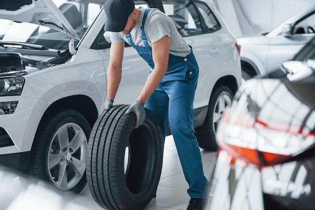 Necesito darme prisa. mecánico sosteniendo un neumático en el taller de reparación. reemplazo de neumáticos de invierno y verano