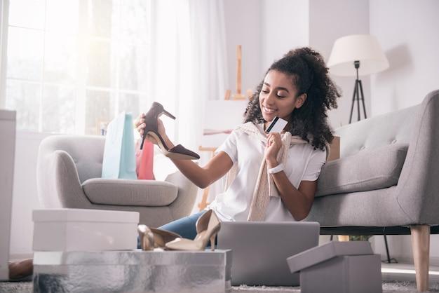 Necesito más. mujer positiva encantada comprando un nuevo par de zapatos mientras es adicto a las compras