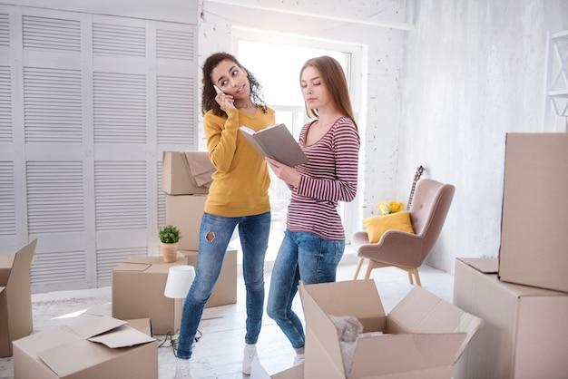 Necesito tu ayuda. encantadora joven haciendo una llamada a la empresa de mudanzas, necesitando su ayuda para mudarse, mientras su amiga busca otro número de teléfono