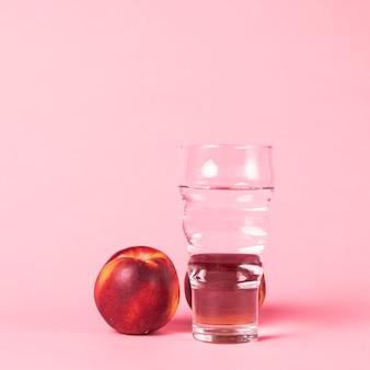 Nectarina y agua sobre fondo rosa