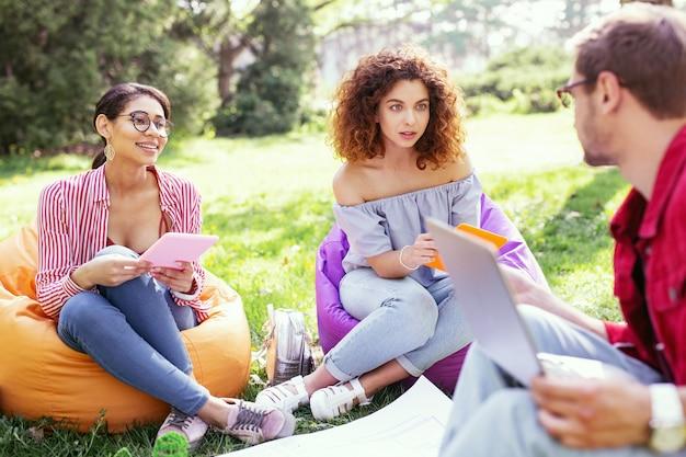 Negociaciones importantes. alerta a mujer morena sentada en la silla y negociando con sus compañeros de trabajo