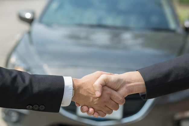 Negocio automotriz. cerca de un comerciante de negocios ofrece un coche al nuevo propietario y un apretón de manos entre dos felicitaciones a los clientes. filtro de tono al aire libre soleado por la mañana.