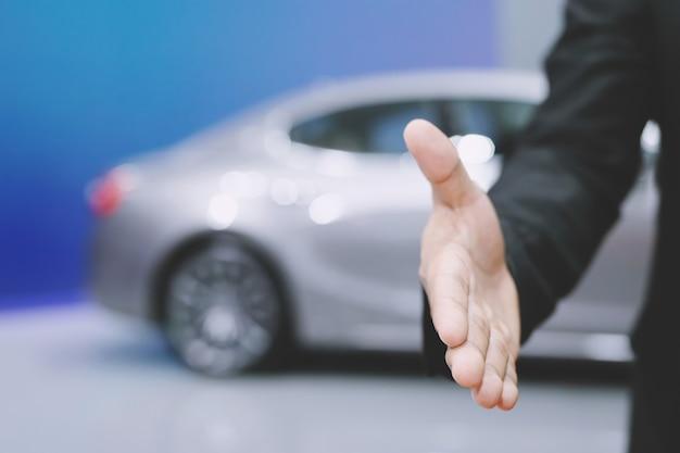 Negocio automotriz. cerca de un distribuidor de hombre de negocios ofrece un coche al nuevo propietario y un apretón de manos entre dos felicitaciones a los clientes. filtro de tono al aire libre soleado por la mañana.