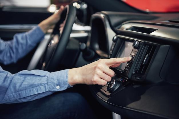 Negocio automotriz, venta de automóviles, consumismo y concepto de personas: mujer feliz que toma el automóvil del concesionario en el salón del automóvil