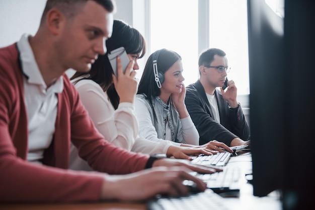 Negocio corporativo. jóvenes que trabajan en el centro de llamadas. se acercan nuevas ofertas