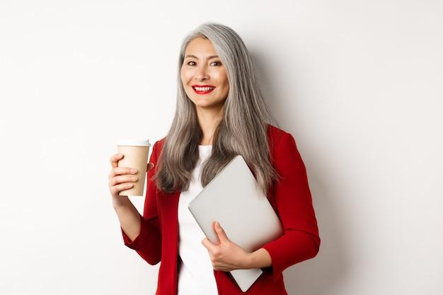 Negocio. exitosa empresaria asiática con cabello gris, vistiendo chaqueta roja, tomando café y de pie con el portátil en la mano, fondo blanco.