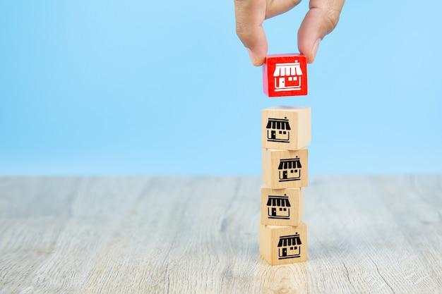 Negocio de franquicia, empresario mano elegir blog de juguete de madera de color reg apilada con iconos de marketing de franquicia tienda