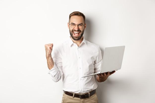 Negocio. gerente feliz ganando en línea, regocijándose con la bomba de puño, sosteniendo la computadora portátil y triunfando, de pie