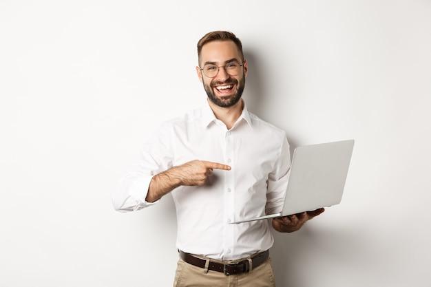 Negocio. gerente guapo en gafas trabajando en equipo portátil, apuntando a la computadora y sonriendo complacido, de pie