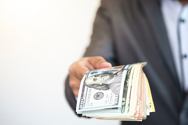 Negocio del gestor del fondo con billetes en dólares estadounidenses y entregándose a alguien