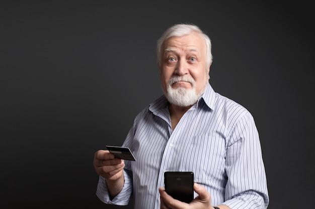Negocio, hombre canoso sosteniendo una tarjeta bancaria y un teléfono y se ve sorprendido