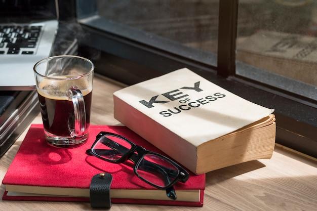 Negocio de libro de éxito, gafas, laptop y café negro.