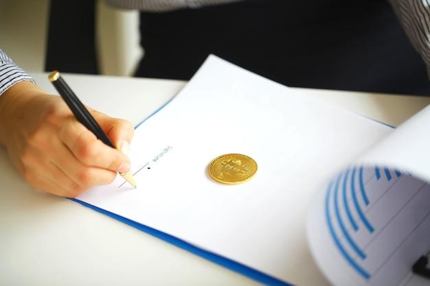 Negocio. manos de mujer con carpeta y bolígrafo. bitcoin en el libro blanco. la mujer escribe una firma en el documento. alta resolución