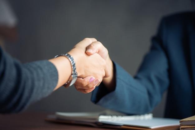 Negocio de negocios, imagen empresaria apretón de manos, feliz con el trabajo, mujer de negocios que está disfrutando con su compañero de trabajo, apretón de manos gestos de la gente acuerdo de trato de conexión. vintage efecto estilo imágenes.