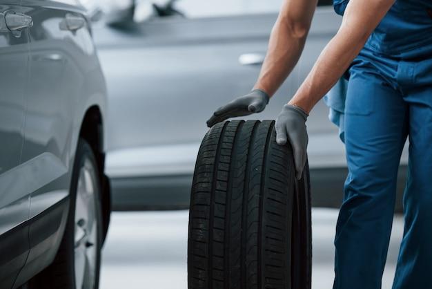Negocio de reparación de automóviles. mecánico sosteniendo un neumático en el taller de reparación. reemplazo de neumáticos de invierno y verano