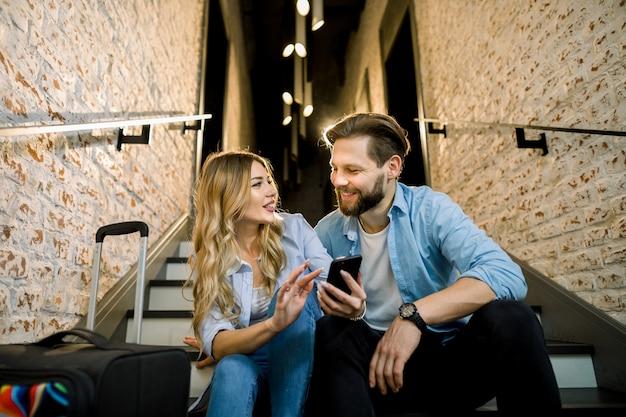 Negocio, tecnología, concepto de viaje: sonriente hombre y mujer con teléfono inteligente sentado en las escaleras de la oficina o el hotel