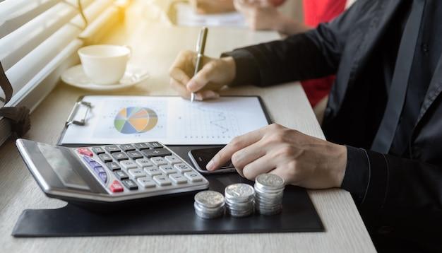 Negocio usando calculadoras, gráfico financiero con monedas de dinero para análisis financiero