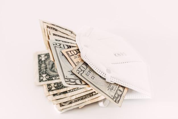 El negocio de vender máscaras nk95, billetes de dólar dentro de la mascarilla sobre fondo blanco.