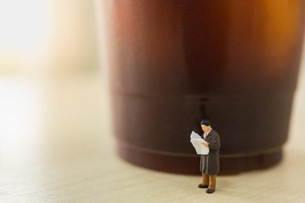 Negocios, concepto de relajación. ciérrese para arriba de la figura miniatura de la gente del hombre de negocios que se coloca que lee el periódico con la taza plástica para llevar de café sólo helado en la tabla de madera.