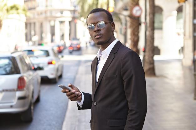 Negocios, estilo de vida y tecnología moderna. ceo atractivo, atractivo, de piel oscura, con ropa formal elegante y sombras usando la aplicación en línea en su teléfono inteligente para solicitar el servicio de taxi, parado en la calle