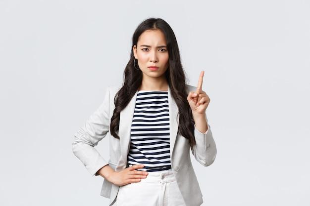 Negocios, finanzas y empleo, concepto de mujeres emprendedoras exitosas. enojada empresaria de aspecto serio enseñando lección a los empleados, agitando el dedo en prohibición, regañando a la persona