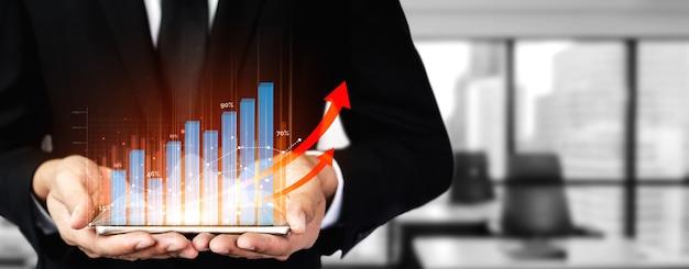 Negocios y finanzas: empresario con gráfico de informes hacia el crecimiento de las ganancias financieras de la inversión en bolsa.