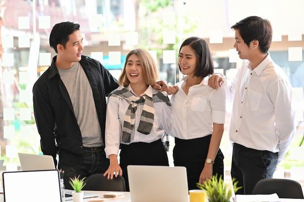 Negocios juntos, cuatro jóvenes empresarios con confianza y motivación se relajan en la oficina moderna.