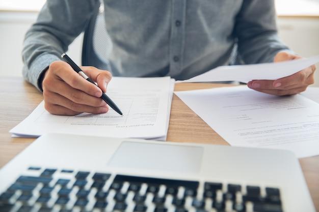 De negocios que controla los documentos en la mesa