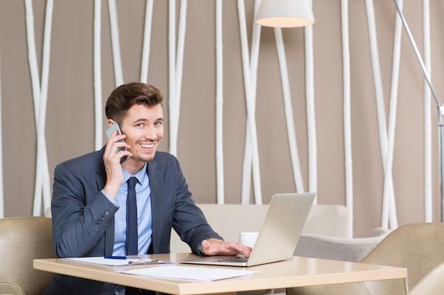 De negocios que trabaja en la computadora portátil y hablando por teléfono
