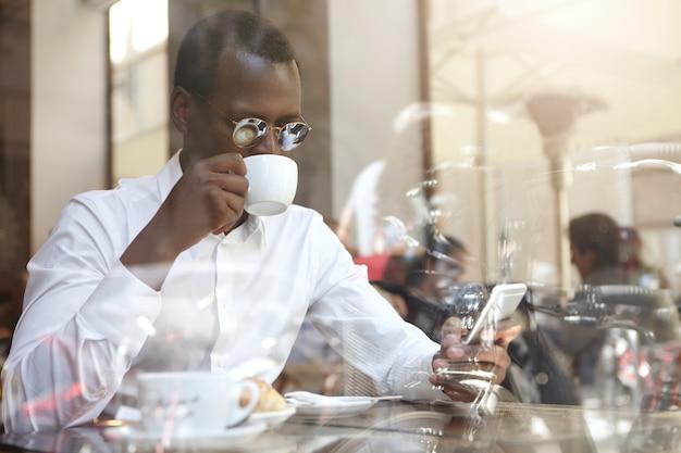 Negocios, tecnología moderna, comunicación y concepto de personas. hombre de negocios afroamericano elegante confiado en gafas de sol redondas bebiendo cappccino en la cafetería, sentado junto a la ventana con teléfono celular