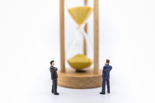 Negocios, trabajo, tiempo y gestión. ciérrese para arriba de la figura miniatura de dos hombres de negocios que se coloca y que mira al reloj de arena.