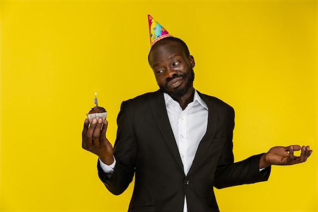 El negro guapo parece perdido mientras sostiene un pastel de cumpleaños