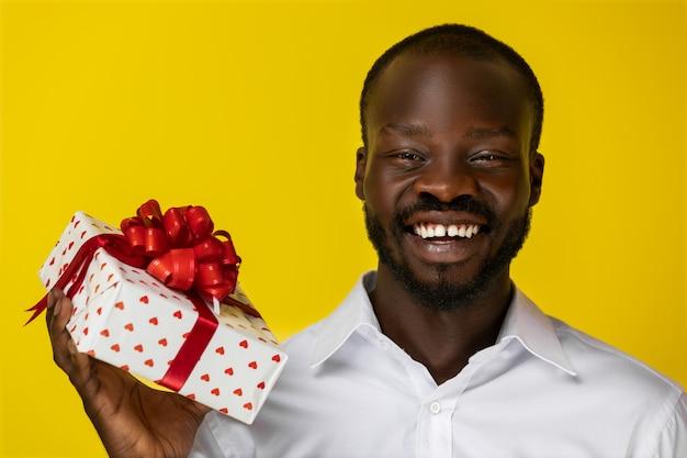 Negro guapo sonriendo a la cámara y sosteniendo una caja de regalo
