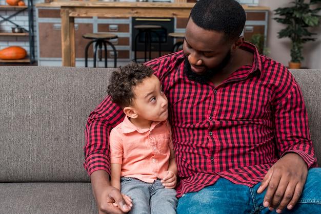 Negro padre e hijo hablando en el sofá