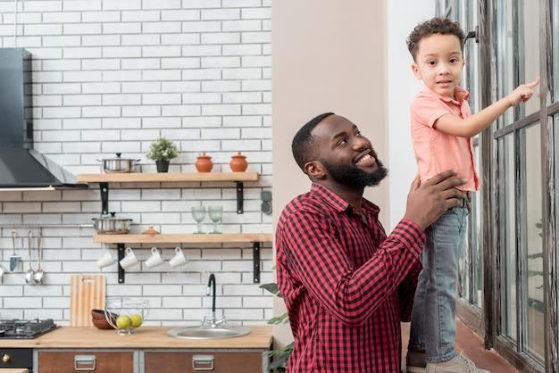 Negro padre e hijo de pie en la ventana apuntando lejos