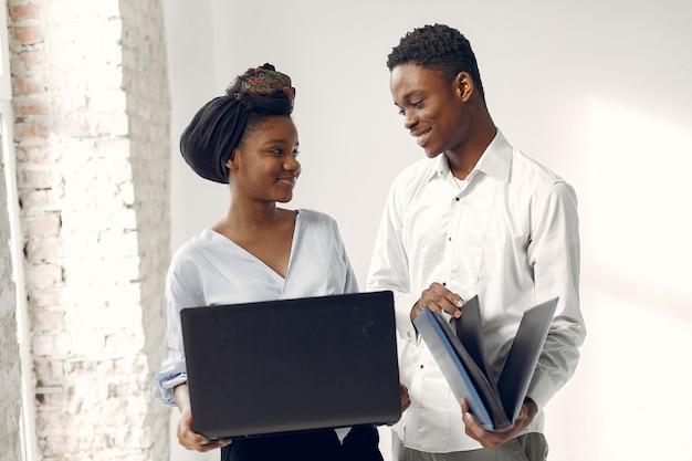 Los negros de pie sobre una pared blanca con una computadora portátil