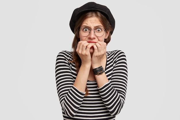Nerviosa mujer parisina se muerde las uñas, mira nerviosamente, se siente avergonzada después del fracaso, tiene los ojos abiertos, usa un suéter a rayas y una boina de moda