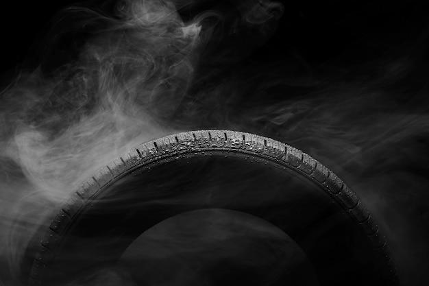 Neumático de automóvil cubierto de gotas de agua en la niebla