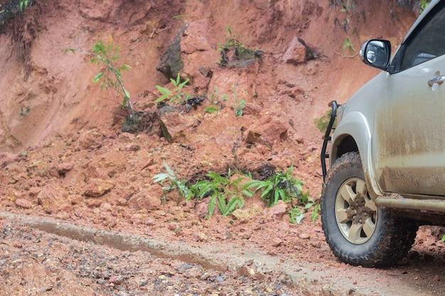 Neumático de coche con deslizamiento de tierra que bloquea el camino de tierra en un bosque.