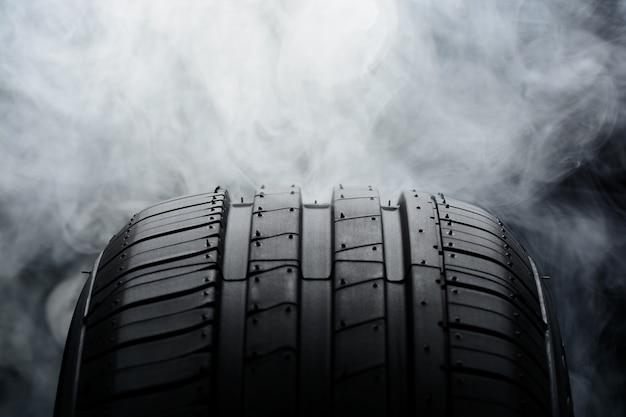 Neumático de coche y humo en negro