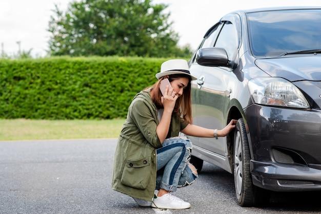 Neumático desinflado del coche. mujer con coche desglosado de neumáticos desinflados en el medio de la calle