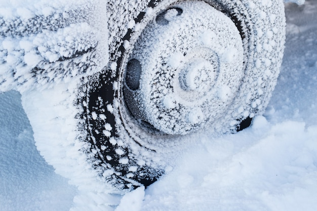 Neumático de invierno coche en camino de nieve. neumáticos en detalle de la carretera nevada.