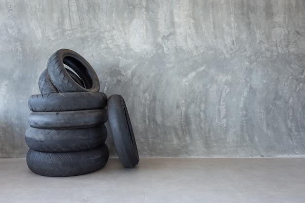 Neumático de moto viejo en pared de cemento desnudo