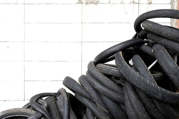 Neumático de motocicleta vieja en la pared de ladrillo