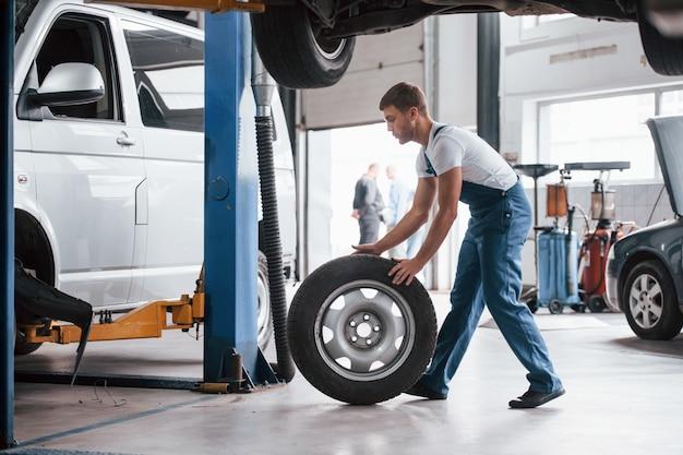 Neumático nuevo. empleado en el uniforme de color azul trabaja en el salón del automóvil